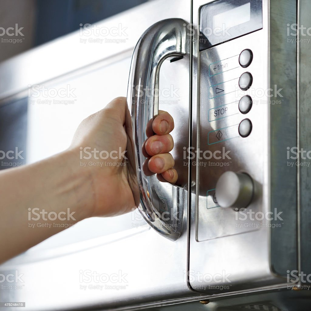 opening of microwave oven door stock photo