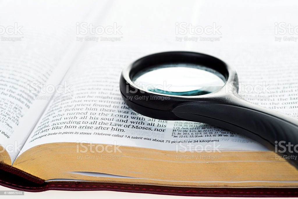 Openning book with magnifying glass stock photo
