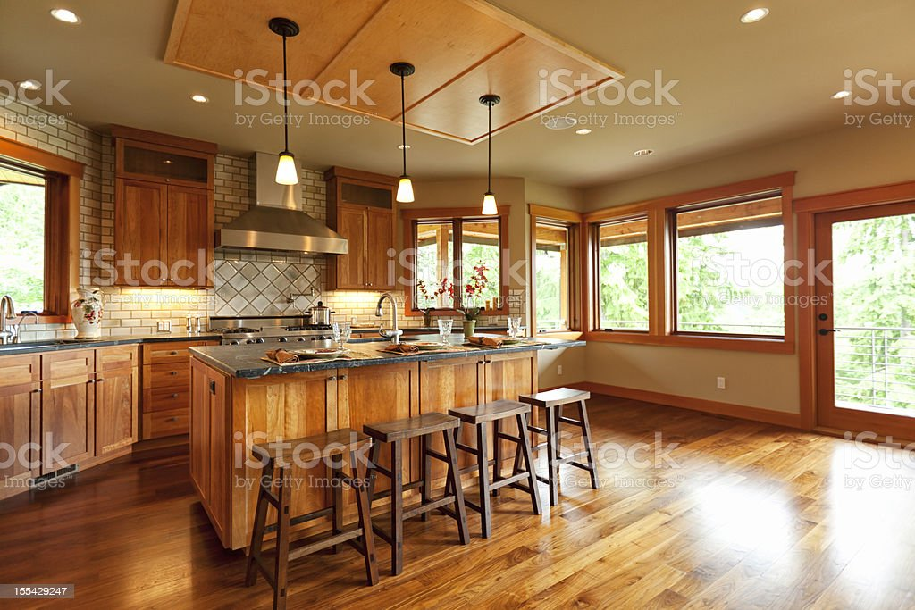 Open-plan kitchen with wooden cabinets and walnut floor stock photo