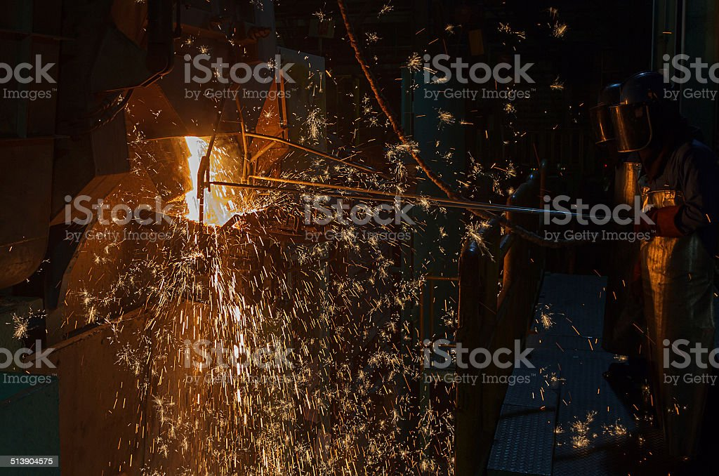 operater tapping molten metal stock photo