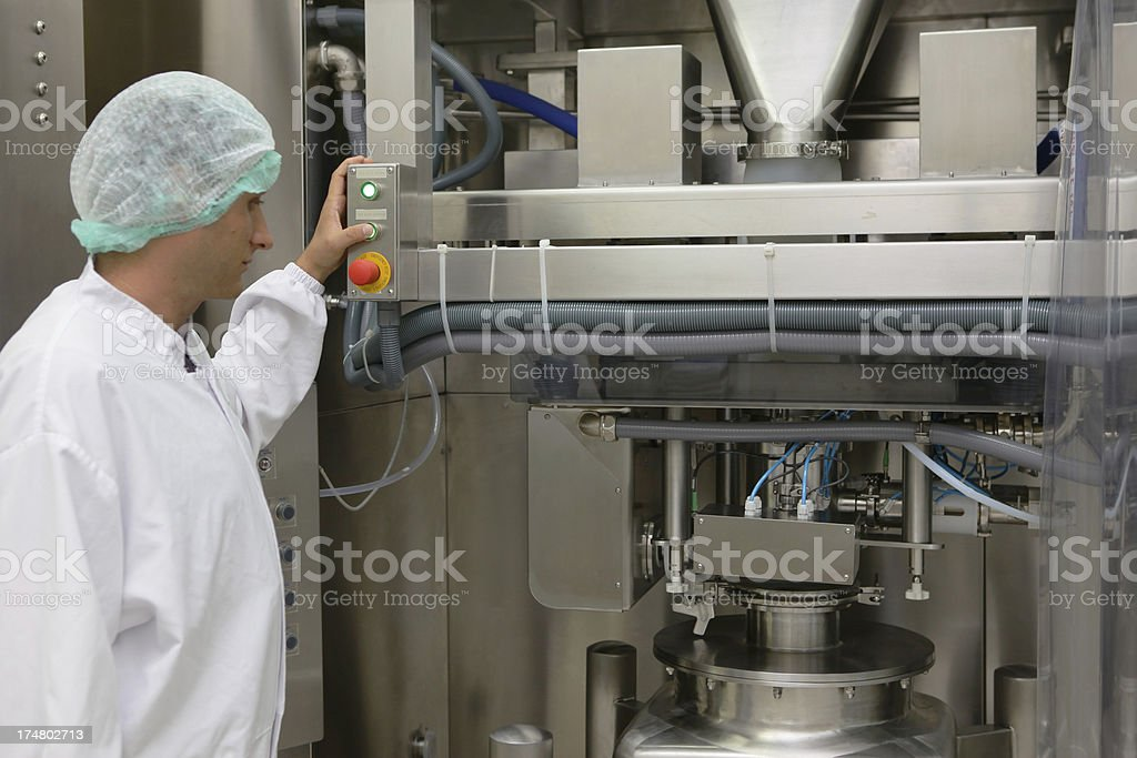 Operating a machine in pharmaceutical factory stock photo
