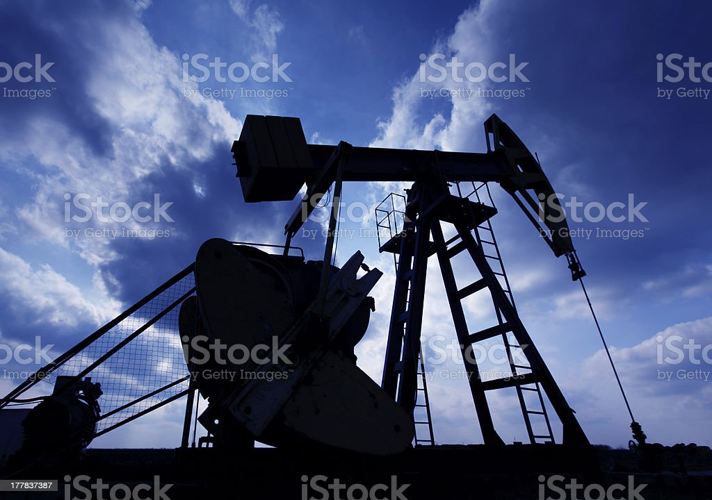 Operating oil well contour profiled on sky stock photo
