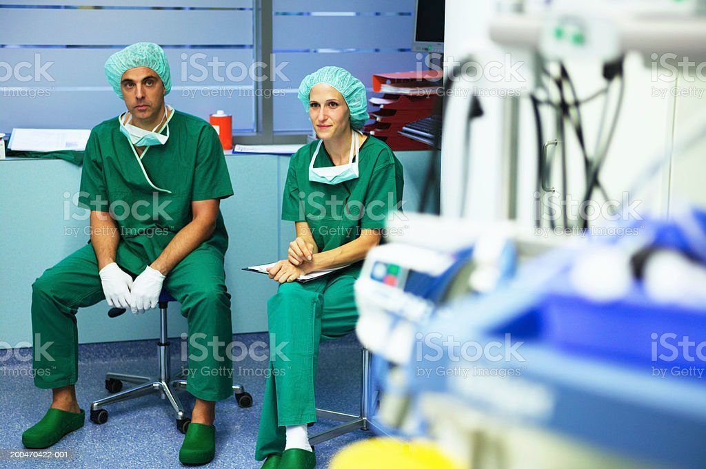 Operating theatre staff sitting on stools in theatre, wearing scrubs royalty-free stock photo