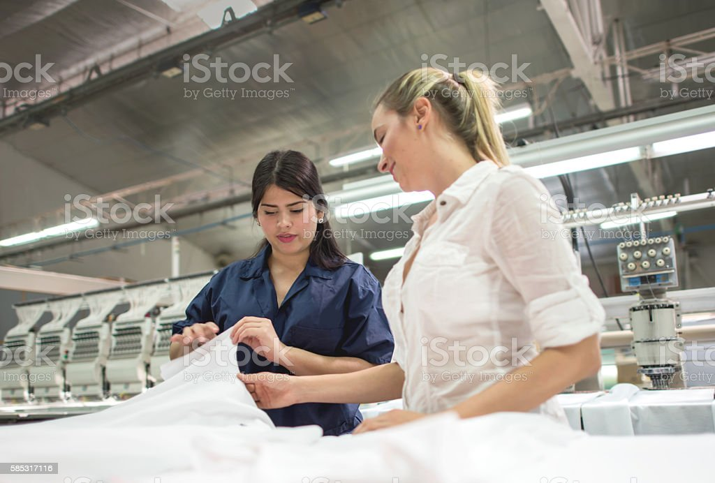Operator at a clothing factory talking to business owner stock photo