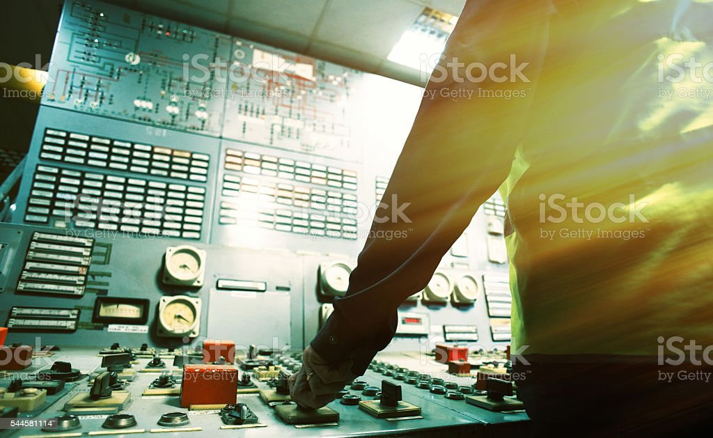 operator hand on the control panel power plant stock photo