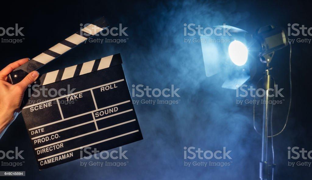 Operator holding clapperboard, studio light on background stock photo