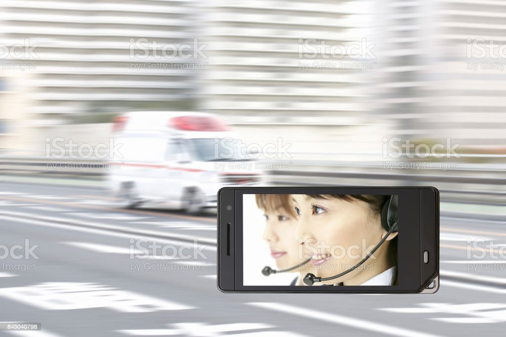 Operator on the mobile screen and an ambulance stock photo