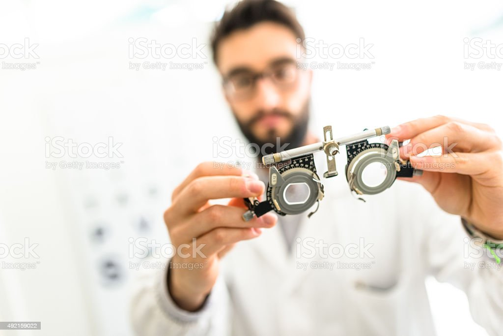Ophthalmologist doctor looking a phoropter glasses stock photo