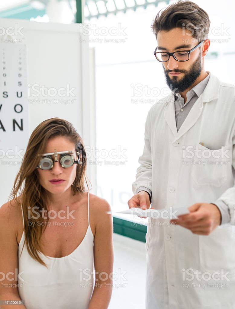 Ophthalmologist doctor reading the diagnosis at the patient stock photo