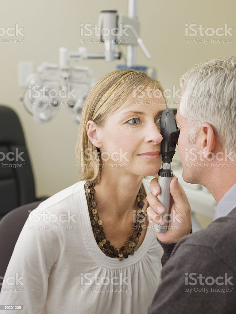 Ophthalmologist giving patient eye exam stock photo