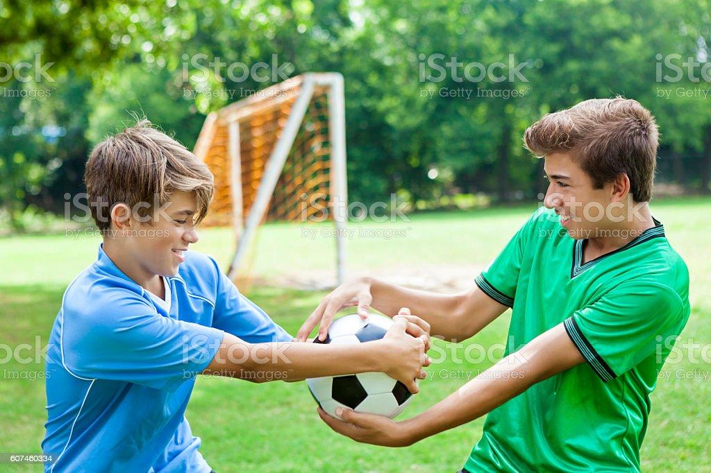 Opposing soccer team players fight over ball stock photo