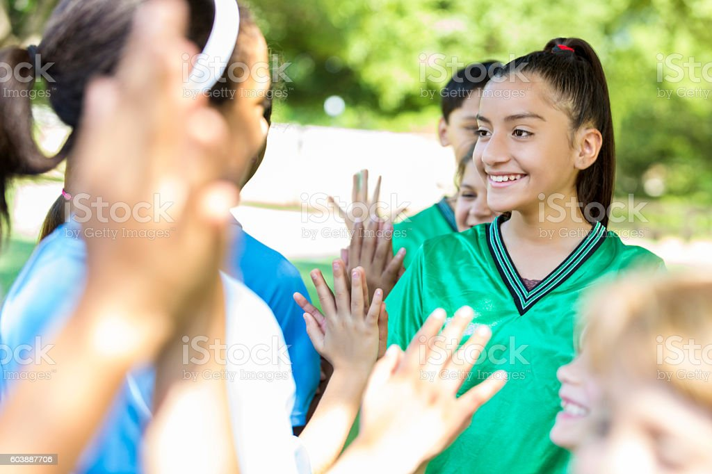 Opposing soccer teams line up for high fives after game stock photo
