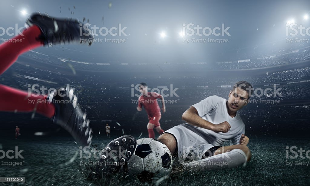 Opposing soccer teams wrestling for the ball in a stadium stock photo
