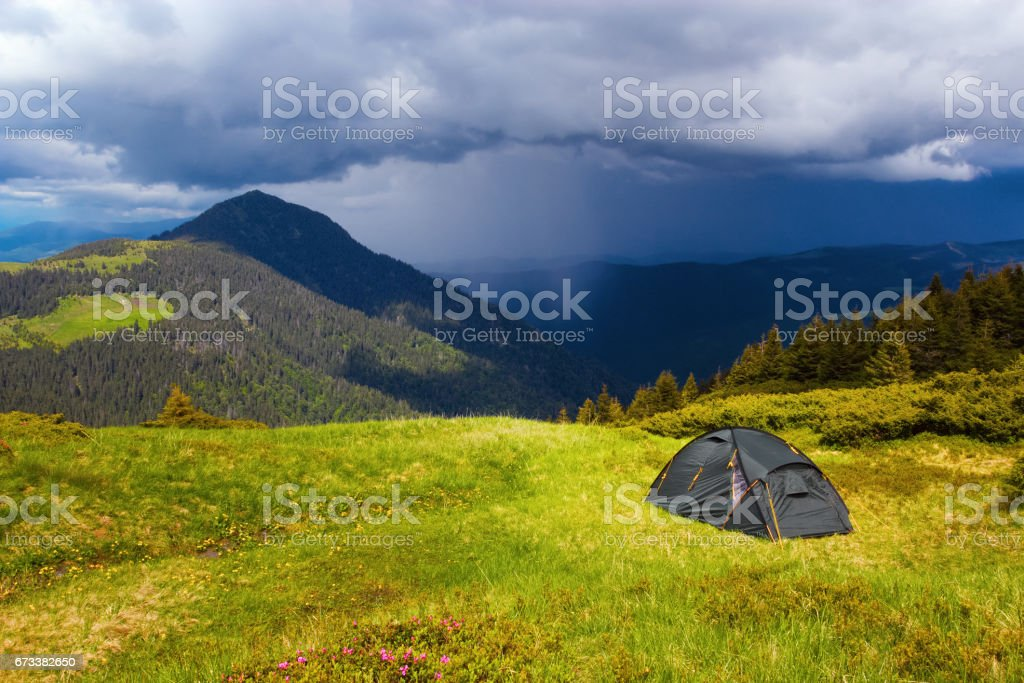 Opposite a high green mountain stands a tourist tent with a view on the beautiful stormy sky on a summer day. stock photo