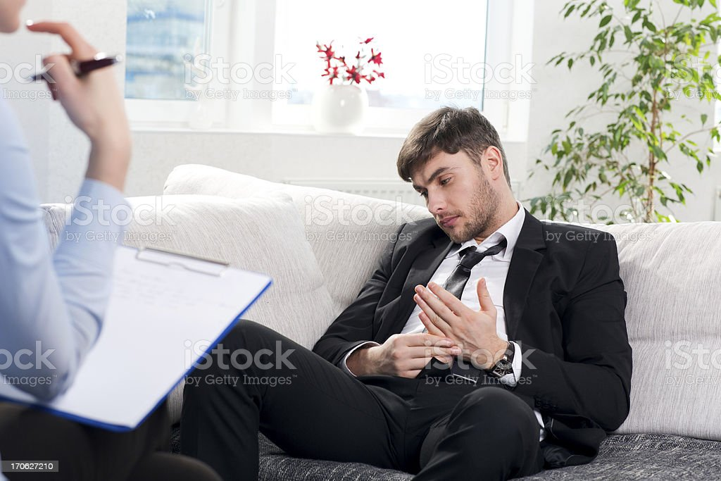 Oppressed man talking with psychologist royalty-free stock photo