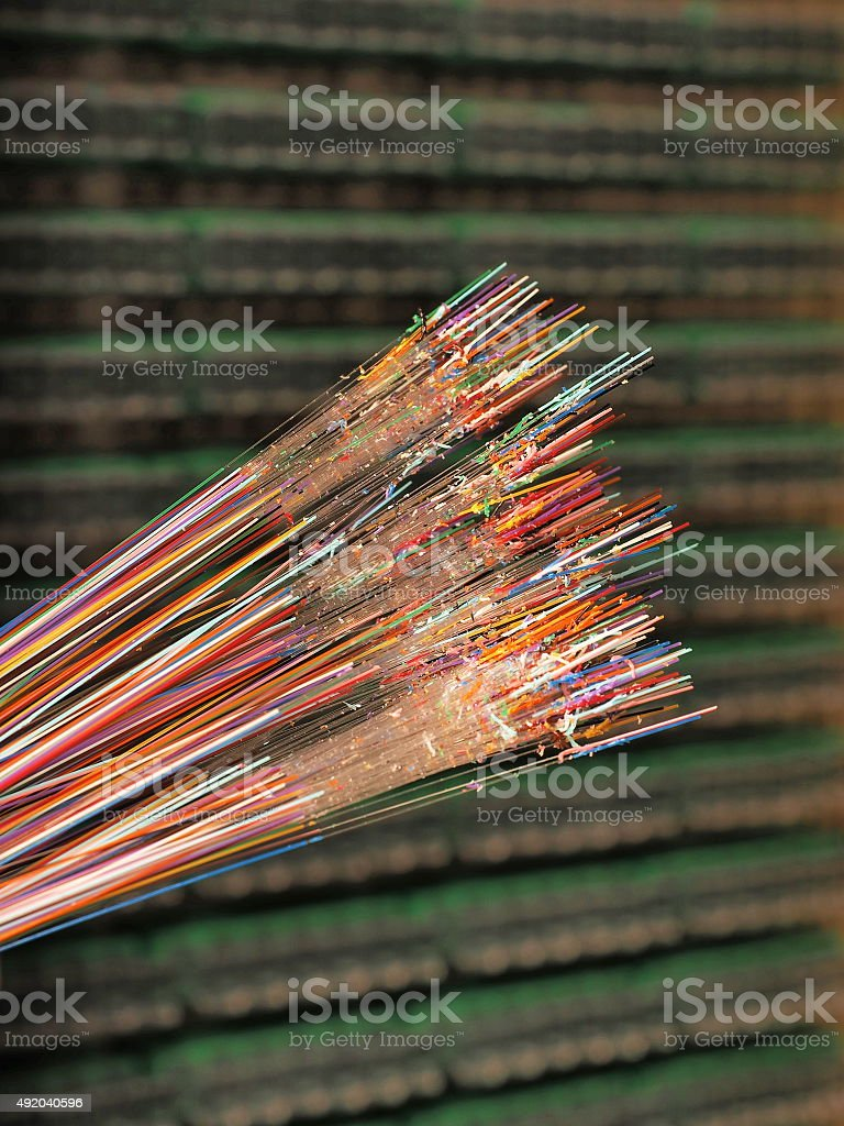 Optical fibers of 12 different colors with stripped color layer stock photo