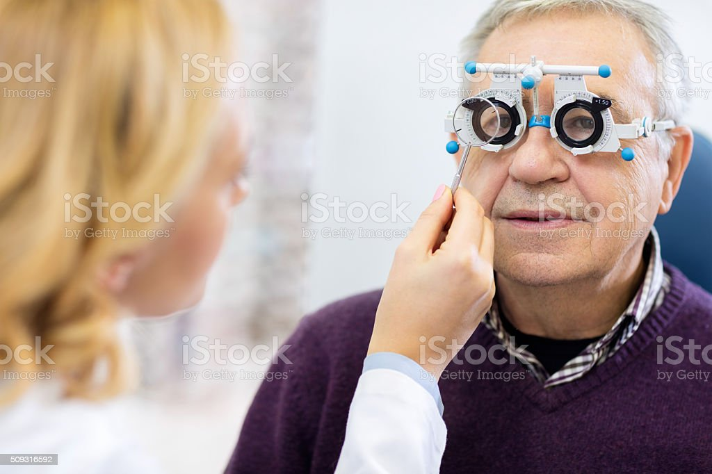 Optical specialists precisely determines diopter to senior patie stock photo