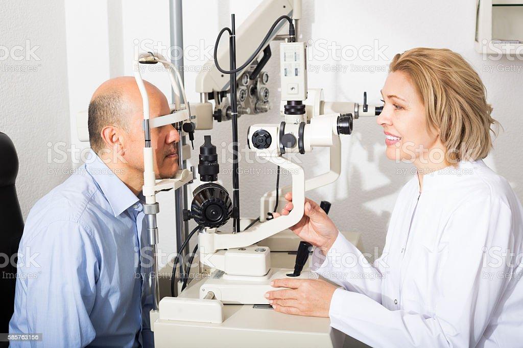 Optician doing eye check up stock photo