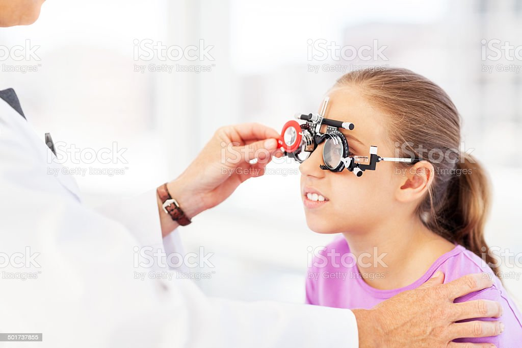 Optician Examining Girl's Vision In Clinic stock photo