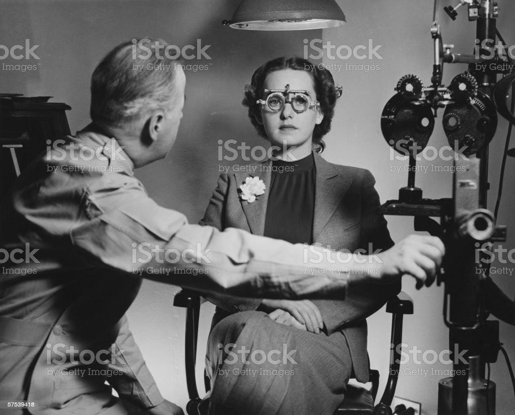 Optician examining patient's eyes, (B&W) stock photo