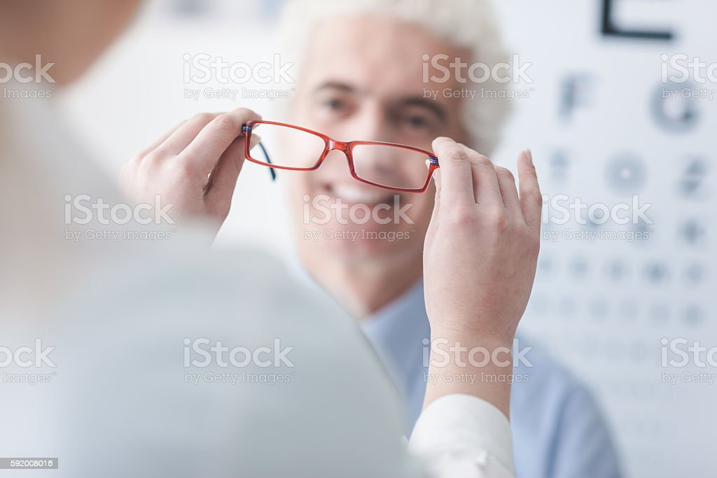 Optician giving new glasses to the patient stock photo