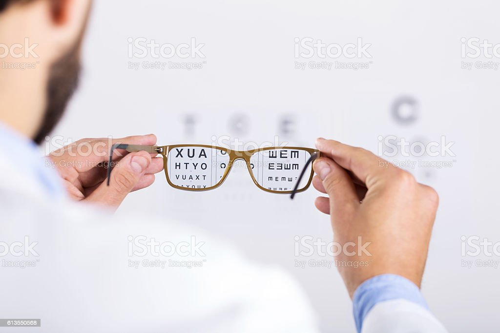 optician holds glasses in front of eyesight test chart stock photo