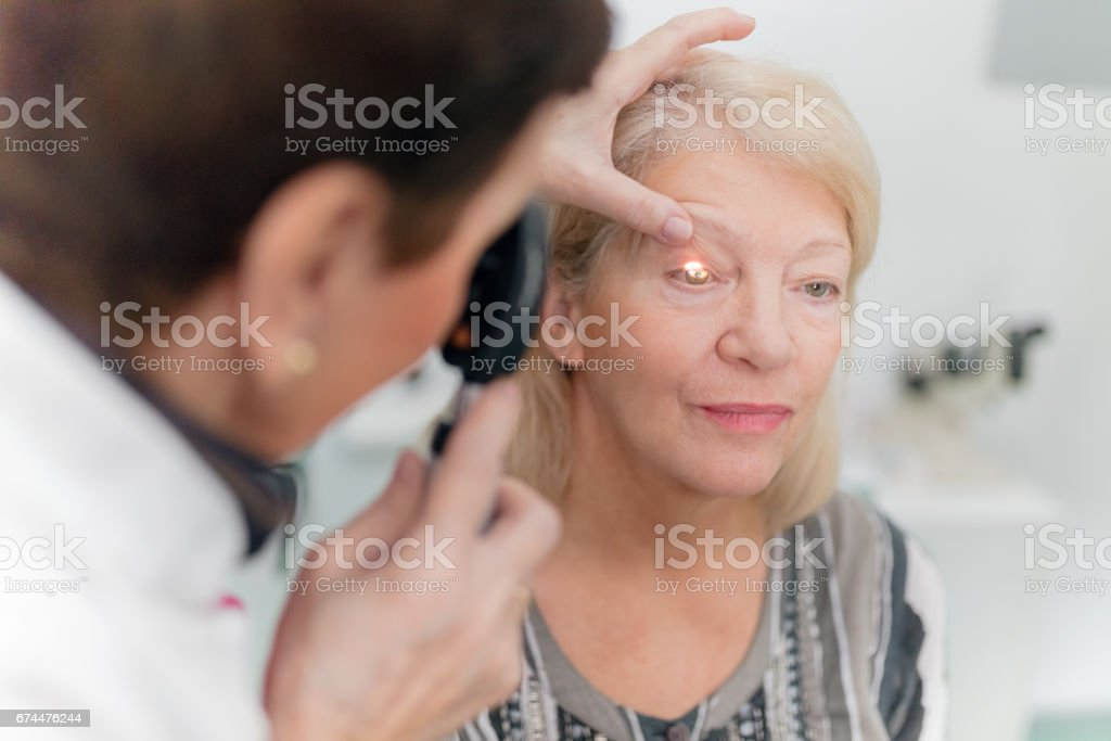Optician looking into patients eyes stock photo