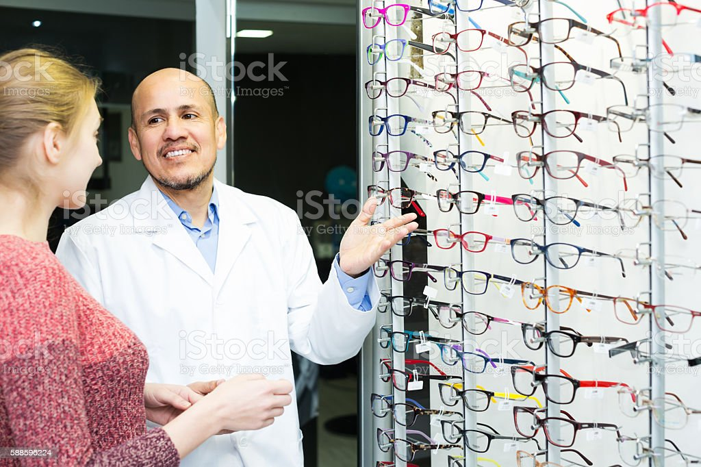 Optician offering glasses to woman stock photo