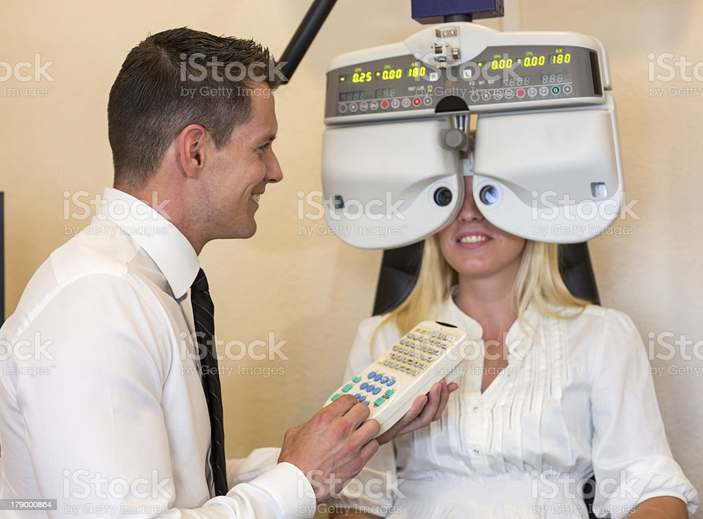 Optician or optometrist and patient with a phoropter royalty-free stock photo