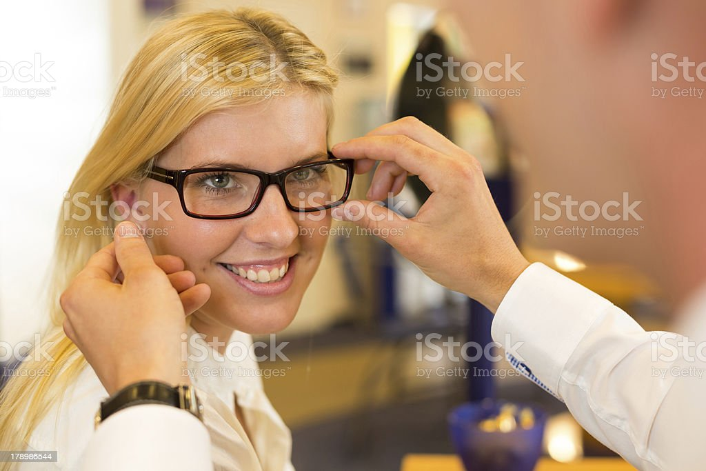 Optician or optometrist consulting a customer about eyeglasses royalty-free stock photo