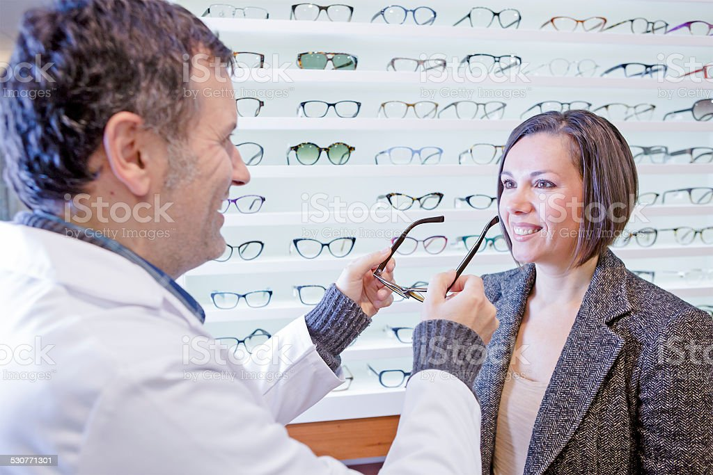 optician trying on glasses to a customer stock photo