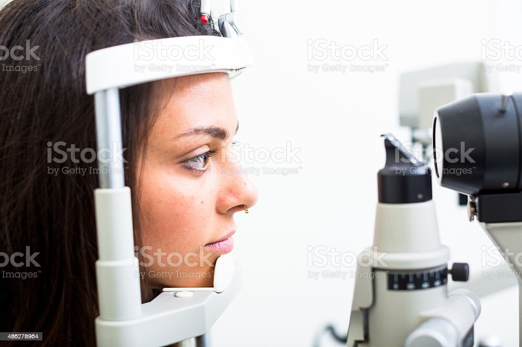 Optician visiting young woman to check her eyesight. stock photo