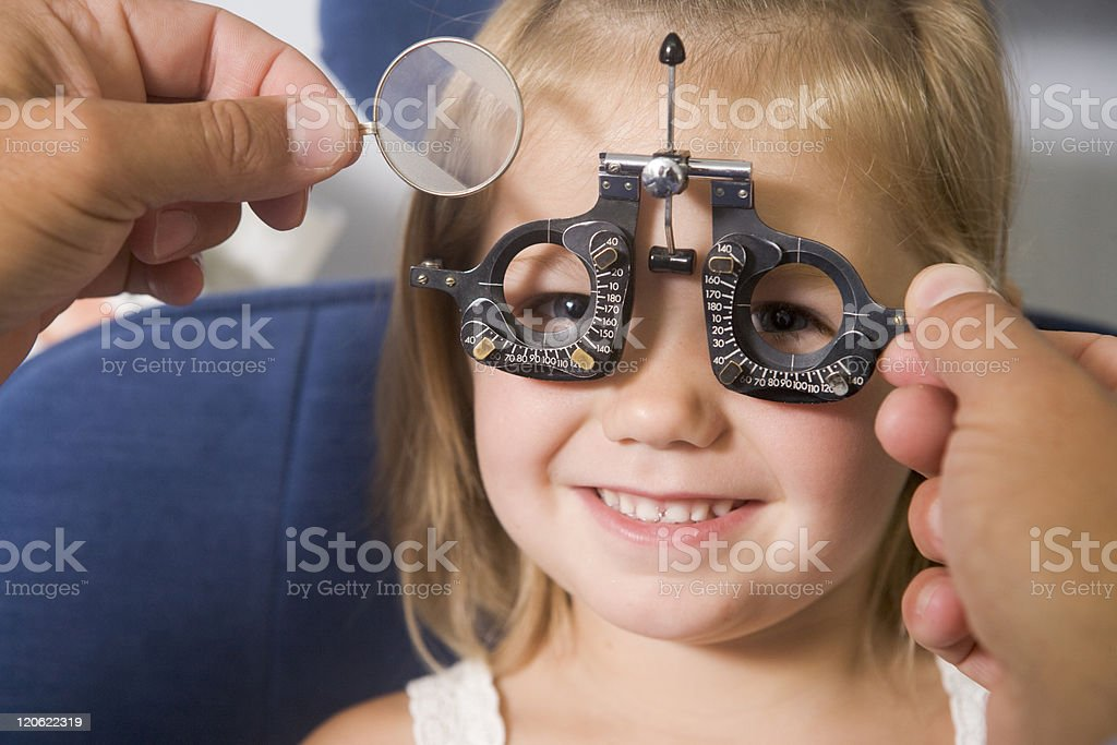 Optometrist giving young girl an eye examination stock photo