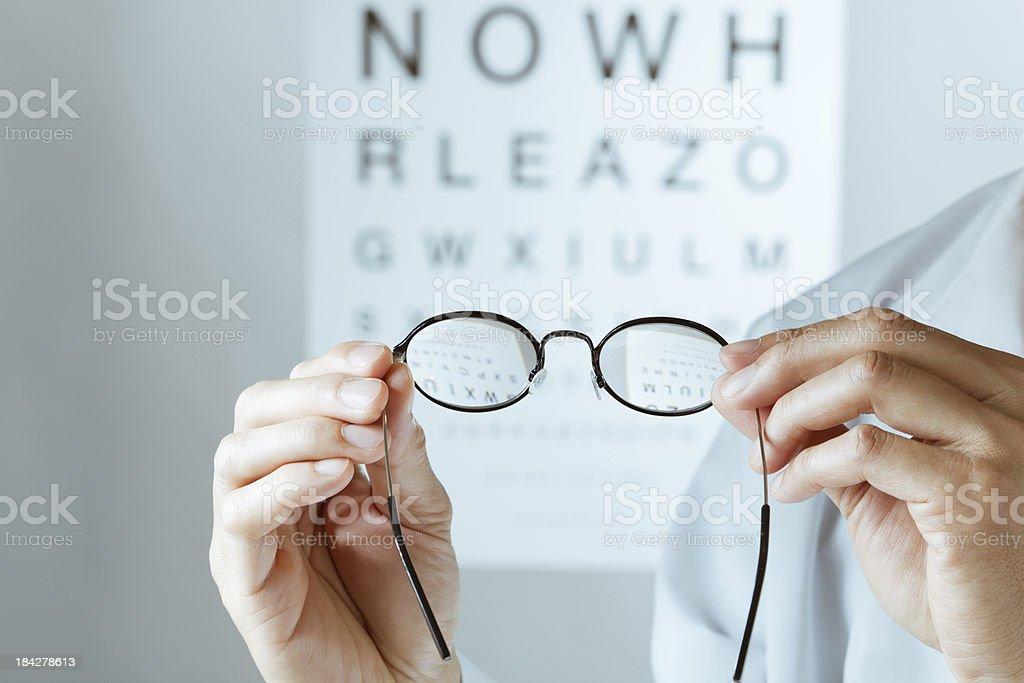 Optometrist Holding Eyeglasses Conducting Eye Chart Examination Hz stock photo