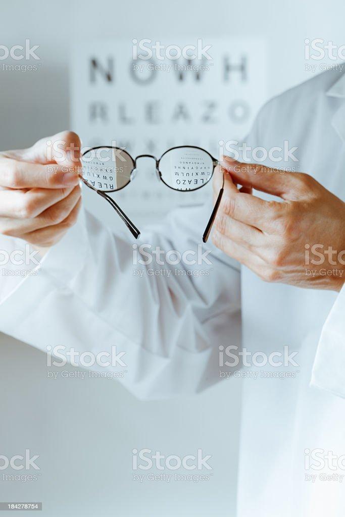 Optometrist Holding Eyeglasses Lens Over Eye Chart for Medical Examination stock photo