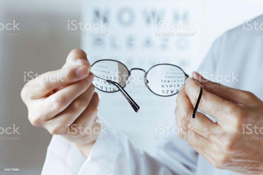 Optometrist Holding Glasses Conducting Eye Chart Examination Hz royalty-free stock photo