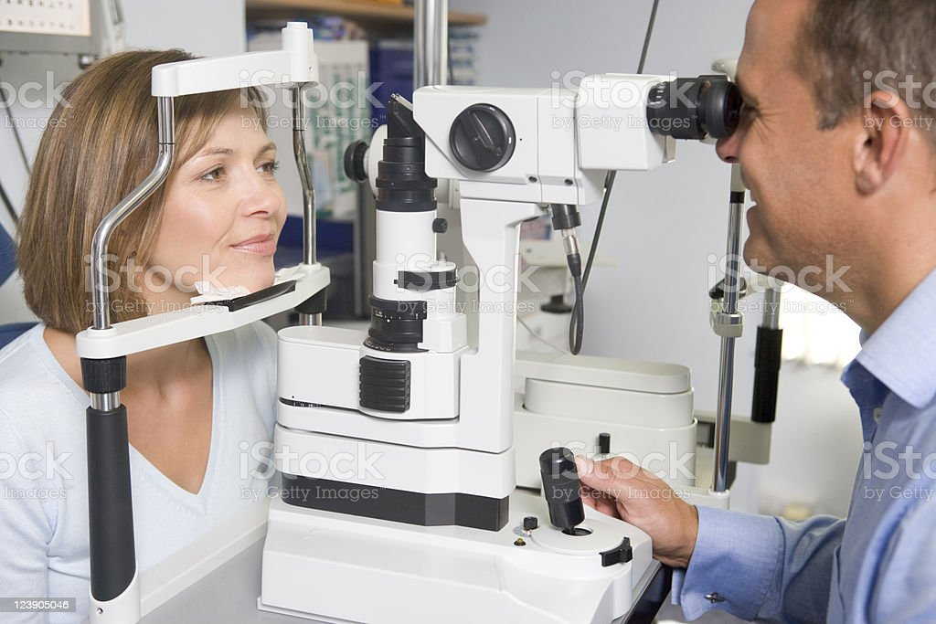 Optometrist in exam room with woman looking into machine stock photo