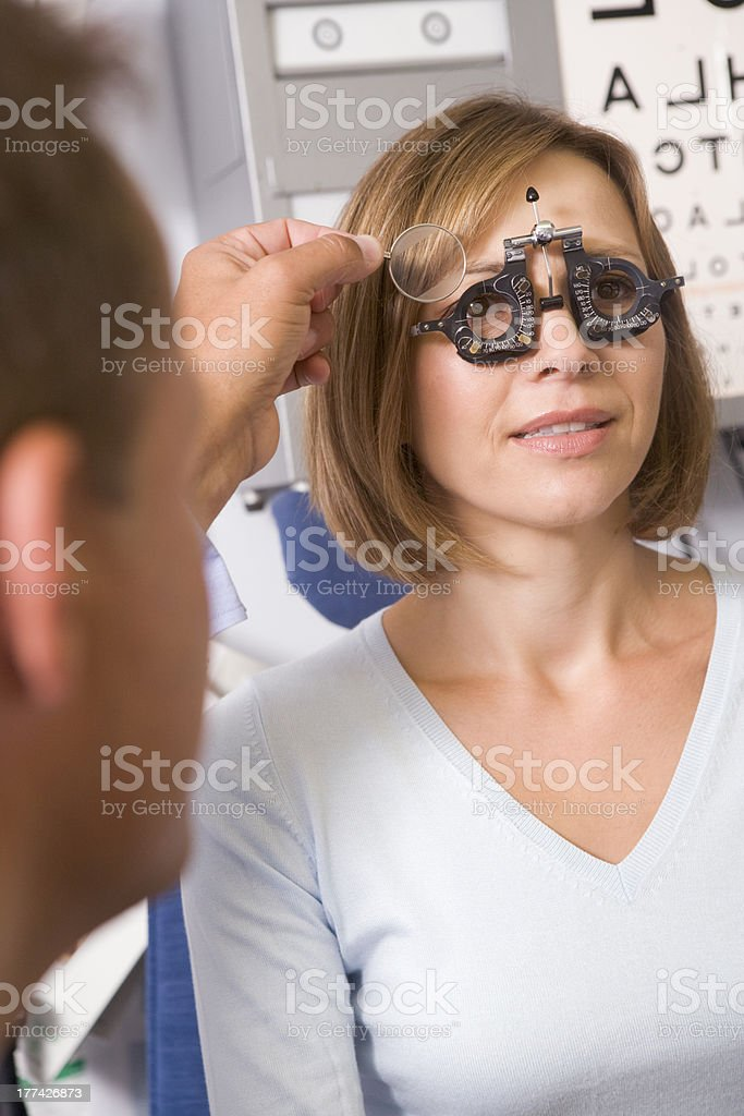 Optometrist in exam room with woman on chair royalty-free stock photo