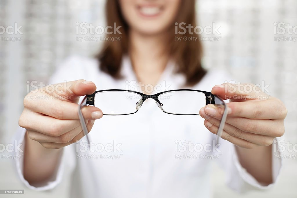 optometrist, optician giving glasses  to try stock photo