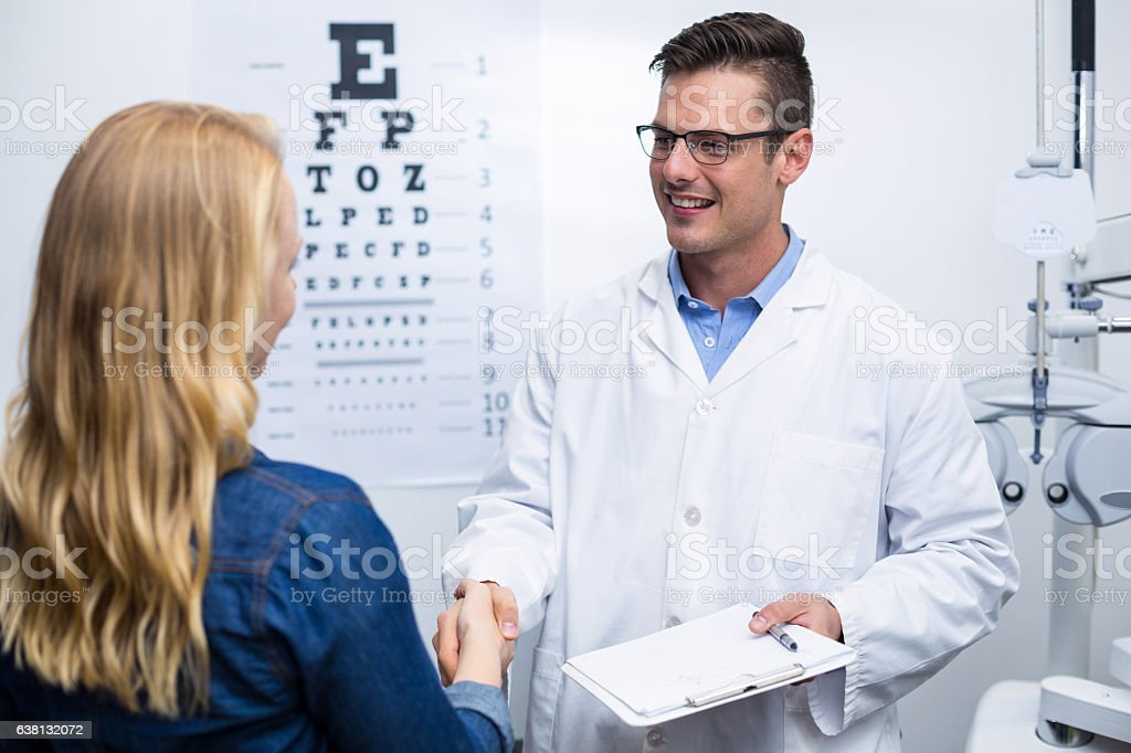 Optometrist shaking hands with female patient stock photo