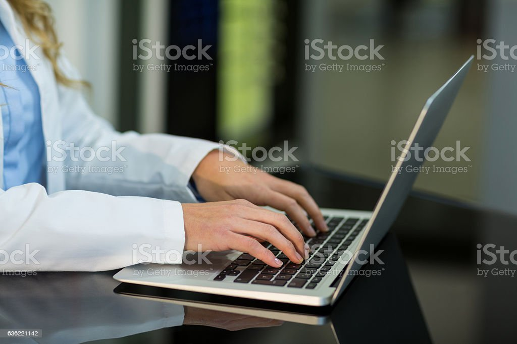 Optometrist using laptop in ophthalmology clinic stock photo