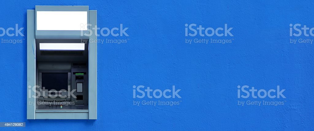 ATM Or ABM Or Cashpoint Machine Byilt-In The Blue Wall stock photo