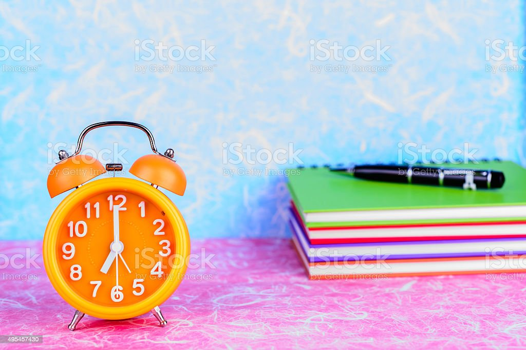 orange alarm clock on table with note book and pen stock photo