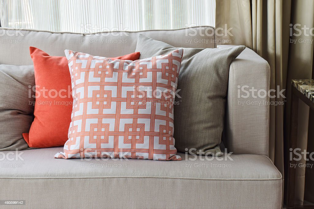 orange and and gray pillows on sofa stock photo
