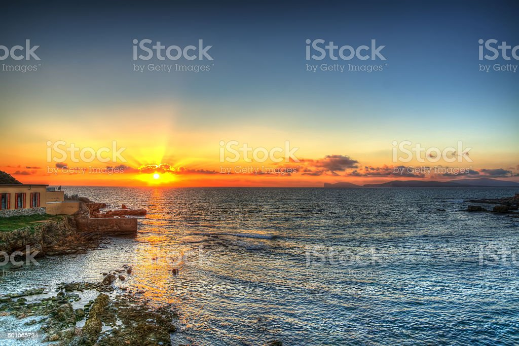 orange and blue sky over Alghero at sunset stock photo
