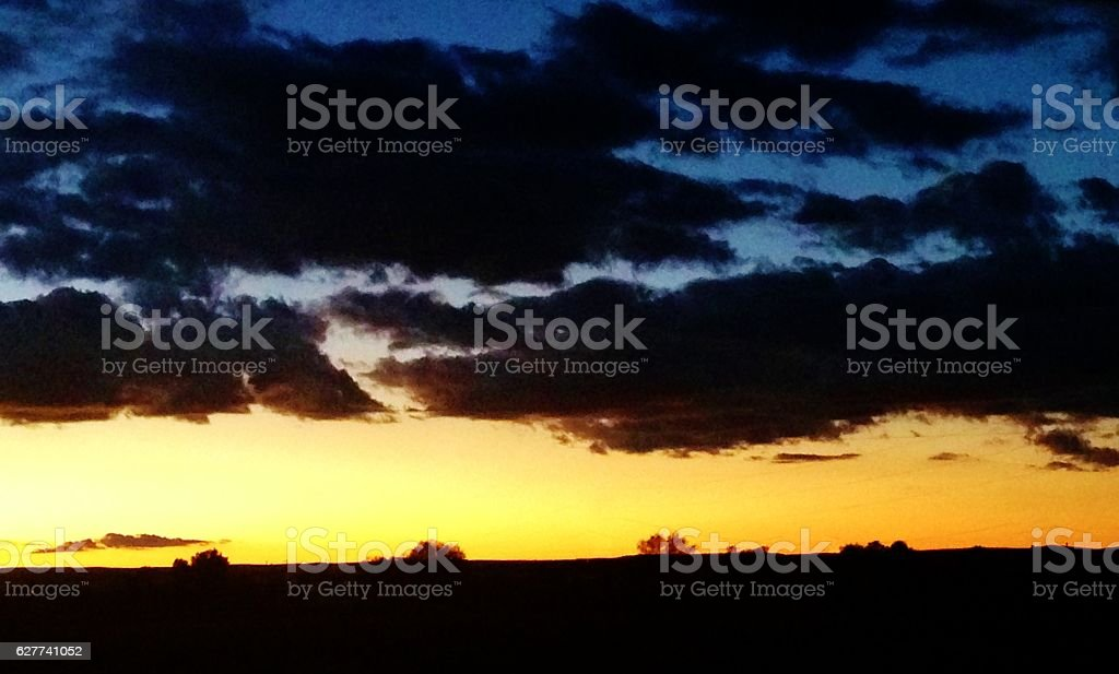 Orange and Blue Sky with Dark Clouds stock photo