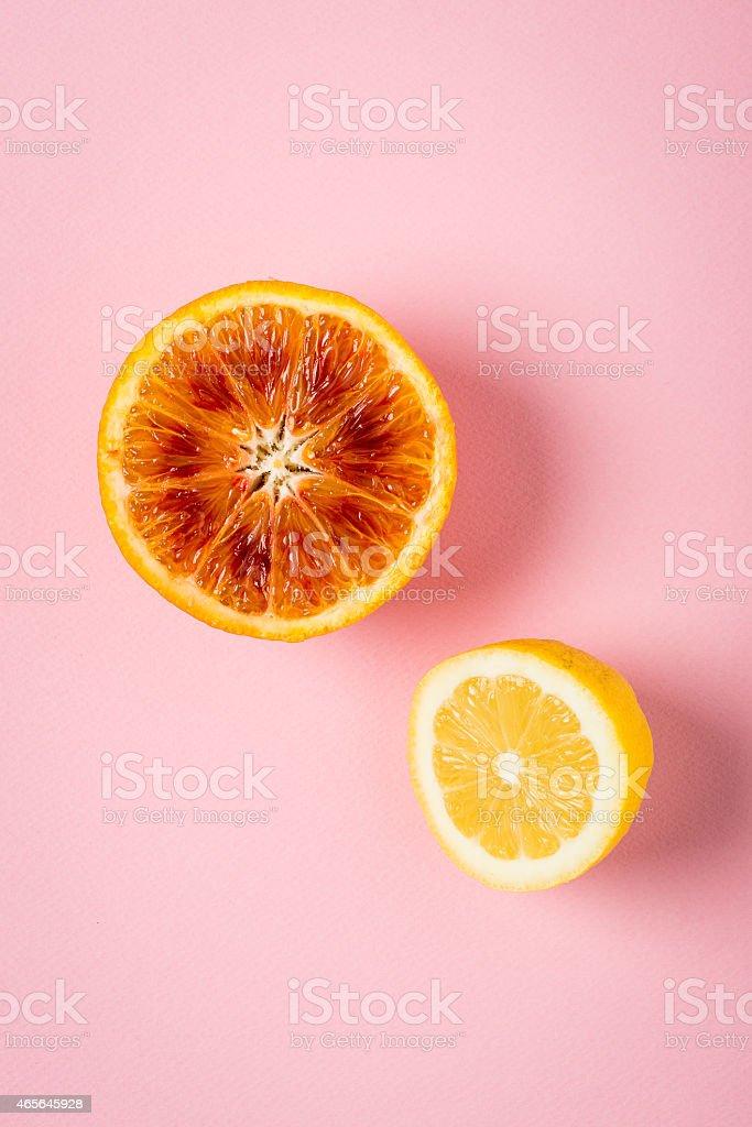 Orange and lemon on pink paper background, minimalist still life stock photo