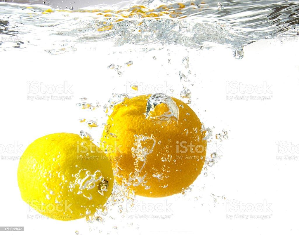 orange and lemon splashing into water royalty-free stock photo