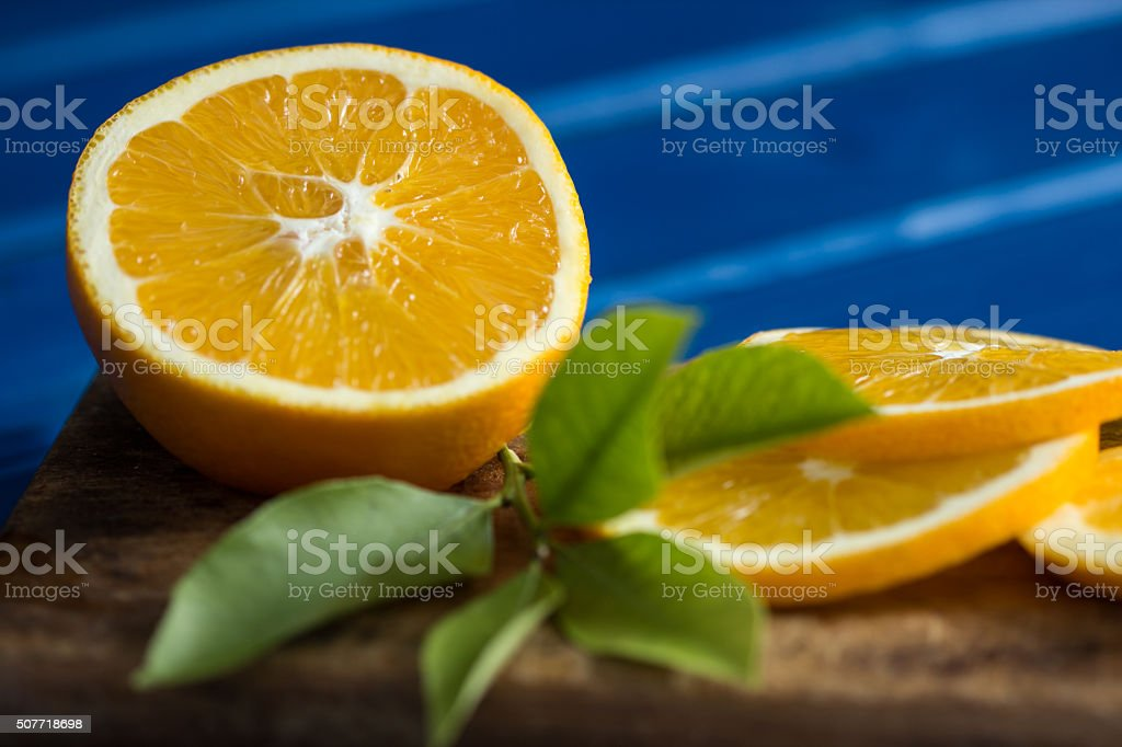 Orange and orange slices on blue wooden background royalty-free stock photo