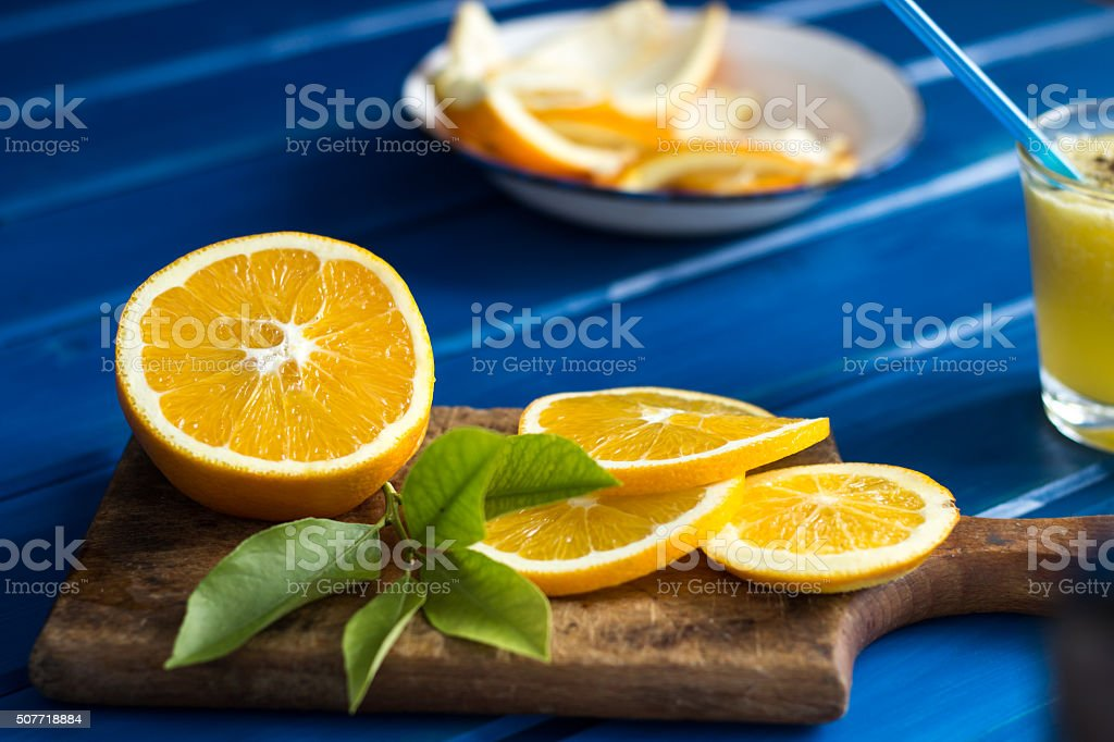 Orange and orange slices on blue wooden background royalty-free stock photo
